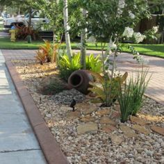 Rocks, gravel, drought resistant plants.... add succulents and It will be perfect for the front yard!