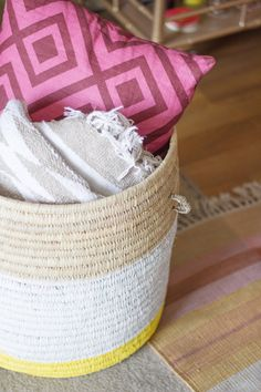 DIY Painted Woven Basket. Your roommates are sure to appreciate how tidy you are with this basket, that you can use for dirty clothes or miscellaneous stuff!