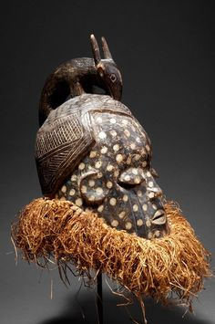 Congo, Suku. Mask with dense ruff out of raffia and a carved antelope on the head.