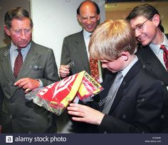 Download this stock image: Prince Harry (2nd R) unpacks a 1998 French soccer scarf he was given as his father, Britain's Prince Charles (L) looks on, before the 1998 Soccer World Cup group G match between England and Colombia, June 26. England won 2-0 and qualified for the second round of the competition to play against Argentina on June 30. In center is British Ambassador to France Sir Michael Jay. Man on Right is unidentified.    JD/WS - GTD63R from Alamy's library of millions ...