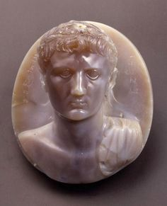 """This """"Bust of Augustus' dates back to about 75 after Christ, it probably made in Rome. Auguste wears the crown of oak leaves, falling strips of the head and spreading over to the front shoulders whose left shoulder is draped. Eleven small holes on the crown suggest that it was adorned with acorns or gold leaf."""
