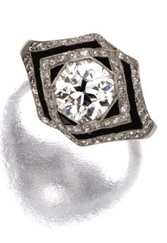 DIAMOND AND ONYX RING, CIRCA 1920 Centering an old European-cut diamond weighing approximately 1.45 carats, within a border of narrow interwoven bands set with calibré-cut onyxes and single-cut diamonds, mounted in platinum, size 5¾.