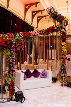 The bride and groom sat in front of a floral and crystal curtain at the Indian wedding reception.