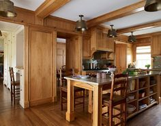Cabinetry, paneling, and beams by CJS Millwork are butternut wood. Architect McKee Patterson designed the island with shelves and drawers on either side, a dining area on one end, a Bosch dishwasher on the other. Barstools are from Wood & Hogan.   - HouseBeautiful.com