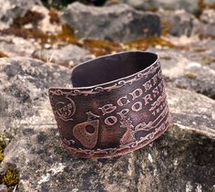 This ouija board bracelet is made of copper, hand cut and polished; its a dimensional piece, with the lighter areas raised and the darker ones