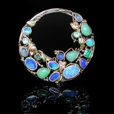 Sibyl Dunlop (in the style of, according to the seller but I am sure this is by Dorrie Nossiter). An Arts and Crafts era brooch set with seventeen gemstones including opal, moonstone, jade and emerald. Unhallmarked gold and silver construction. Diameter 55mm. Weight 17.4g. I think this is perhaps more likely to be by Dorrie Nossiter - she made many brooches in this elliptical circular style. Sold by Kayes.
