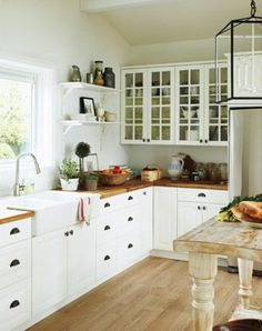 "wood counters, white, window in front of sink, glass front cabinets. a non-counter ""island"""