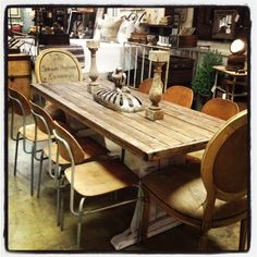 Old Farm table from the midwest with antique industrial school chairs and head chairs covered in antique German grain sacks featuring a crown.