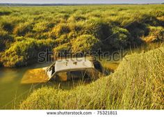 """An old rusted out car in a river """"Marismas del Odiel"""", Huelva, Spain"""