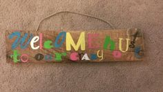 Welcome to our crazy house hand painted wooden sign 13 x 3, multi colored, repurposed wood, jute twine hanger, $15 contact gingerlyunique@gmail.com for orders