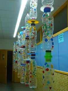 mooie wandversiering van aan elkaar gekoppelde én versierde plastic flessen. Onder een lamp gehangen geeft het een supermooi effect