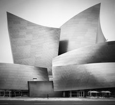 """Casey Dunn - This building looks familiar, but since the series was titled, """"Quiet City"""" I'm not too sure where this building is located! regardless, I love that the photographer placed  the image in black & white because the gradation of the curved steel walls are beautiful and I feel that might have been lost if the image were in colour. The single person in the foreground gives the photo a nice sense of life because while the black & white is nice, it almost seems too drab in my opinion."""