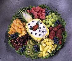 A grand selection of the finest fruits from our Produce Department surround a natural pineapple bowl filled with fruit dip.