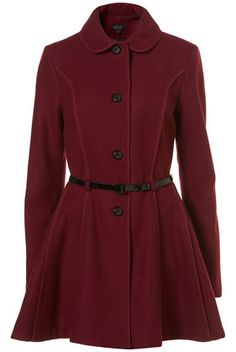 Thigh length skirted plum coat with exposed bound seams, side slit pockets and a black patent belt.