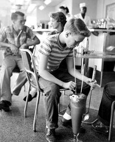 © Genevieve Naylor - Teenager Drinking Large Milkshake. Lincoln, Nebraska, USA 1953.