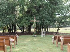 A cross and flower lined aisle complete with wooden pews make us adore this garden wedding!