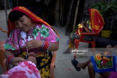 Seeking dailight and refuge from the heat in their houses, Kuna women gather outside at dusk to work on Molas, the traditional Kuna woman's dress, which they hope to sell to tourists visiting the island, on the small island of Corbisky, pop. 200, in El Porvenir, San Blas. San Blas, also known as the Comarca de Kuna Yala, is an autonomous Kuna Indian region stretching some 226 miles on the Caribbean coast from Colombia to Colon, the town north of the Panama Canal. The Kunas, who have their…