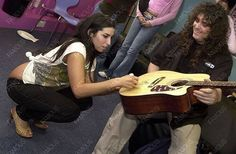 Amy signing an acoustic guitar.