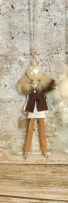Meet Ellies Belle, Hattie, a sophisticated French doll pendant necklace in chocolate brown faux suede pants, a beige and brown fun fur jacket over a white sweater, a rhinestone necklace and a rhinestone crown atop her glass pearl head. Silver, bronze or gold finish body and chain. Each