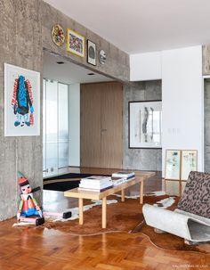 Estrutura de concreto aparente, tapete de pele de vaca e muitos quadros.