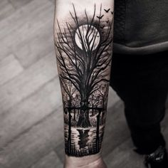 Black and grey tree tattoo on arm