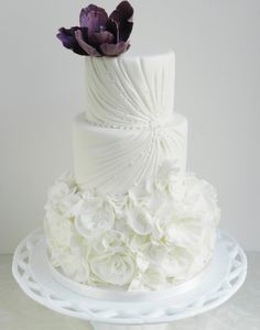 Get inspired: A delicately beautiful wedding cake bedecked with white florals, and topped with a deeply romantic purple flower!  via @MODwedding