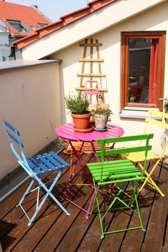 I love these little spaces outdoor with a small table and some chairs. This is such a pretty idea because of the bright colors