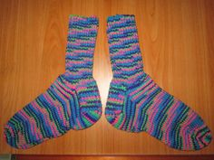 Here is a wonderful pair of hand knit adult size socks. The color is called Bright Mix. Heel to toe is approx. 9 1/2 in. and the ribbing on the top (top to ankle) is approx. 6 1/2 in. These socks are made of 100% acrylic yarn and can be machine washed and dried.
