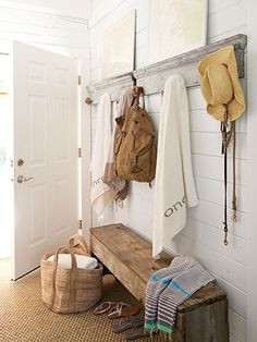 This mudroom is decorated with upcycled finds — salvaged door frames (with rope balls for hooks) and a bench crafted from reclaimed barn wood.