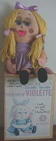 """1963 Shrinkin Violette often referred to as Shrinking Violet, 17"""" tall, stuffed cloth doll, talker with pull string, eyes and mouth moved when she talked, printed face with blue eyes, yellow yarn pigtail hair with violet ribbons, violet dress, white socks and black mary jane shoes that are (I think) non-removable. Marked:  Quality Originals by Mattel Shrinkin' Violette ©1963 The Funny Company."""