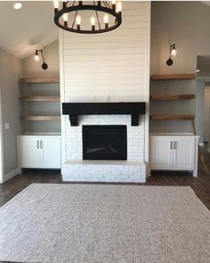 Love the white brick. We want a mantle with a brown reclaimed wood to coordinate with floor color. Built ins on side possibly a barn door to close in t.v. If possible. Shiplap painted white going up to ceiling. We do like the idea of using the color from island in kitchen on the sides of fireplace to connect both rooms. Accent wall if you must.
