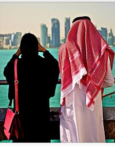 A Qatari couple watching the Doha skyline from the Museum of Islamic Art