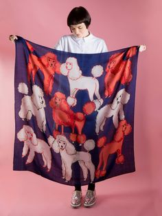 The piece of cloth which the woman is holding is a pattern on poodles which are in the same colors
