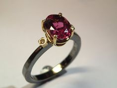 Alternative engagement solitaire ring with pink tourmaline and two diamonds. An…