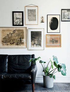 neutral gallery wall above black leather sofa