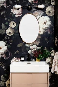 This petite powder room features a bold floral wallpaper and oval mirror.