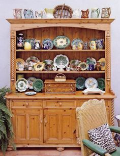 Majolica pottery looks so pretty when it is massed together.  The collection looks perfect on this old pine cabinet, and I  like how they used the top of the cabinet also.