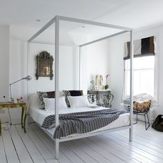 """The combination of a sleek white metal bed frame, an ornate gilt mirror, an industrial table lamp, and a painted wood floor make for an appealing eclectic modern bedroom. Put together a similar look with the following elements."""