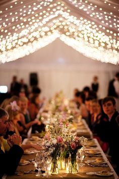 Long wedding tables, jam jar flowers,  and fairy-lights strung on marquee roof