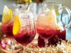 Cranberry Sangría Punch Recipe | This wintry, ruby-red spin on sangria is a staff favorite but comes with a warning: It goes down easy. You can make it a day ahead to make your life that much easier, and just add the Champagne right before serving. Cheers to your new favorite drink for a crowd! Even though cranberries are usually reserved for holidays, you'll be very tempted to make this punch all year long (we won't judge!). This fruity drink has a beautiful ruby red color, so it's a