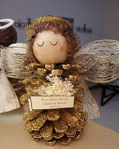 """These little pinecone Christmas angels were made by Lorraine Brown! Here's her tutorial…""""I purchased a Pinecone from Michael's that was already painted and had glitter. I made a bow large enough to be the wings. I purchased a pack of 2″ wooden knobs and the yarn that looked braided from Hobby Lobby for the hair. …"""