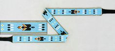 "Native American Beadwork Hat Bands    Navajo Sheri Jackson's wide waterbird and eagle feather hat band is worked in light blue and flame colored 13/14º seed beads accented and edged with metallic gold. The loomwork is 1-1/8"" wide x 22-1/16"" long. It's finished with 7"" long black leather ties.  $214.75"