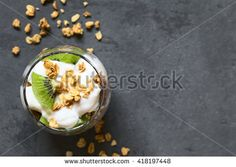 Yogurt parfait with fresh kiwi and crunchy almond and oatmeal granola in glass, photographed overhead on slate with natural light (Selective Focus, Focus on the top of the parfait) - stock photo