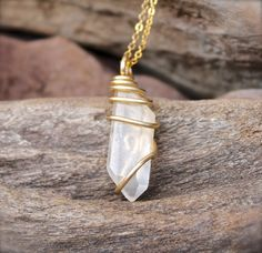 This stunning natural Lemurian seed quartz is all natural. The quartz crystal has been wire wrapped in gold tone wire and measures around