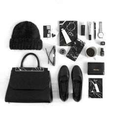Phoebe with her flatlayed black marble essentials, including our Black Marble Camber Satchel