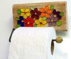 Um verdadeiro jardim de flores coloridas e alegres no seu lavabo. <br>Porta papel higiênico não precisa ser sisudo e sem charme. <br>Esse, criativo e diferente, com certeza, será um diferencial no seu lavabo e irá dar um charme a mais no seu lavabo. <br> <br>A base é madeira maciça e as flores foram recortadas manualmente em pastilhas de vidro cristal. Vem com um gancho de ferro com bolinha de madeira. <br> <br>Tamanho: 17 cm de largura x 13 cm de comprimento.
