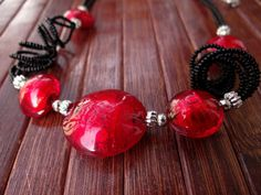"""JOLE  Murano glass parure di VenetianPearls su Etsy.  In this necklace the Murano glass beads are created using gold leaf """"submerged"""", that is melted in the core of the red bead itself. A triple twirled thread of small black beads and small metal parts (nichel-free) links the glass beads, creating a retro effect for a set suited for an elegant evening."""