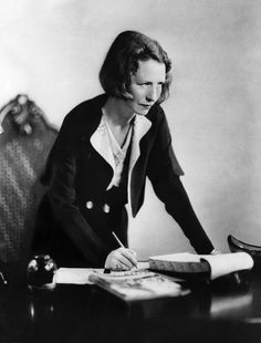 Edna St. Vincent Millay, half-length portrait, standing at desk, facing right…