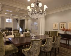 low trio of prints over sideboard & large crystal chandelier; accent host & hostess chairs