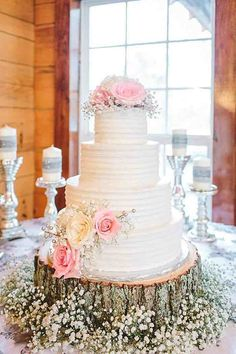 White Three Tier Buttercream wedding Cake with Baby's Breath and Roses